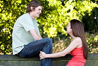 A young couple talking on a park bench