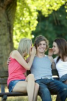 A young man on a bench, two young women whispering to him (thumbnail)