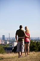 A young couple in a park, looking across the city