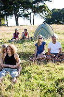 Three young couples sitting in a field near a tent (thumbnail)