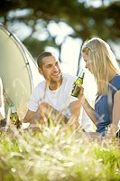A young couple sitting in front of a tent, drinking beer (thumbnail)