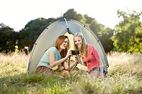 Two young women sitting in a front of a tent, looking at a camera (thumbnail)