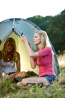 Two young women camping, one applying make_up