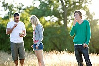 Three young friends standing in a field, eating, drinking and smoking