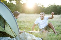 Two young men sitting next to a tent, having a barbecue (thumbnail)