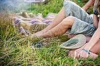 Young couple sitting on the grass, close_up of legs