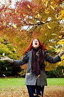 A young woman throwing autumn leaves in the air