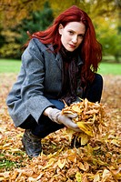 A young woman holding a handful of autumn leaves