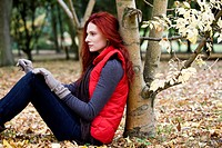 A young woman leaning against a tree, thinking