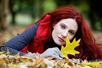 A young woman lying on the ground, holding an autumn leaf