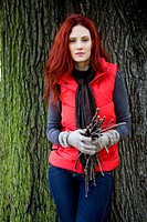 A young woman leaning against a tree, holding a handful of twigs