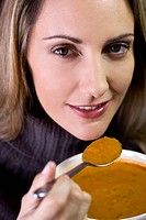 A mid adult woman eating soup (thumbnail)