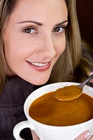 A mid adult woman eating soup