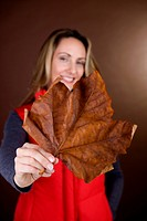 A mid adult woman holding a dried leaf, smiling