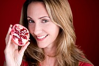 A mid adult woman holding half a pomegranate