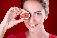 A mid adult woman holding half a fig in front of her eye (thumbnail)