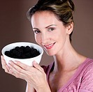 A mid adult woman holding a bowl of blackberries