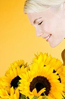 A Young Woman Looking At A Bunch Of Sunflowers