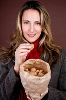 A mid adult woman holding a bag full of mixed nuts