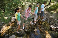 Four teenagers 16_17 crossing stream holding hands elevated view