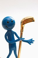 A blue smiley face figure holds up a brass golf club