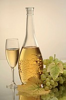 A bottle and a glasss of white wine with white grapes