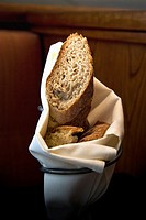 Fresh baked sliced bread in a vertical wrought iron bread holder with a folded linen napkin holding it together