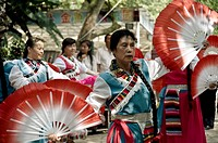 Woman dancing with fans in a park. Kunming, China