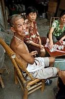 man smoking and playing cards. Ping Le, China