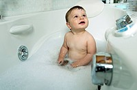 Baby boy taking bath in tub