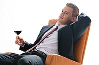 Young man in business suit sitting with glass of red wine (thumbnail)