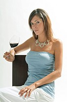 Young woman sitting with glass of red wine (thumbnail)