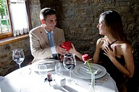 Young man giving a present to young woman at restaurant table