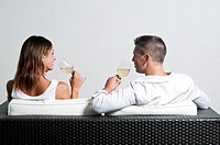 View of couple from the back sitting on couch drinking white wine