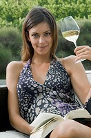Young woman sitting on couch in vineyard with white wine and a book