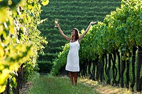 Young woman in vineyard holding wine glass with arms outstretched