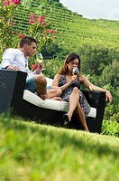 Young couple sitting on couch in vineyard with white wine
