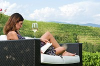 Young woman sitting on couch in vineyard with white wine reading a book