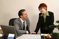 Businessman sitting in an office with his secretary standing beside him