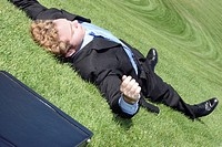 Business man has finally had it, collapses into relaxation on the green hill of tranquility