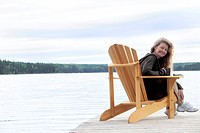 Woman with cup seated on deck chair on dock, Clear Lake, Manitoba, Canada