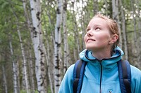 Young girl looks upward in grove of poplars, Manitoba, Canada