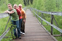 Three women posed on boardwalk nature trail, Riding Mountain National Park, Manitoba, Canada