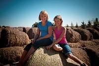Two girls, 10 and 12, seat on bales of straw, Redvers, Saskatchewan, Canada