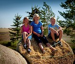 Three tween kids seated on bale, Redvers, Saskatchewan, Canada