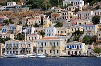 Yachts and private boats in front of colorful traditional houses at Symi port, Symi island, Greece