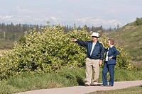 Elderly couple walking on a path and pointing