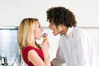 domestic life: interracial couple eating an ice cream