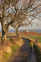 alnmouth, northumberland, england, a woman walking along a road by the ocean