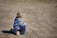 young boy sitting on a piece of wood